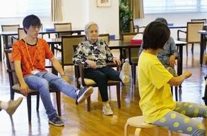 有料老人ホームで、高齢者と一緒に転倒予防の体操をする荒川弘憲さん(左)=2017年8月、東京都内